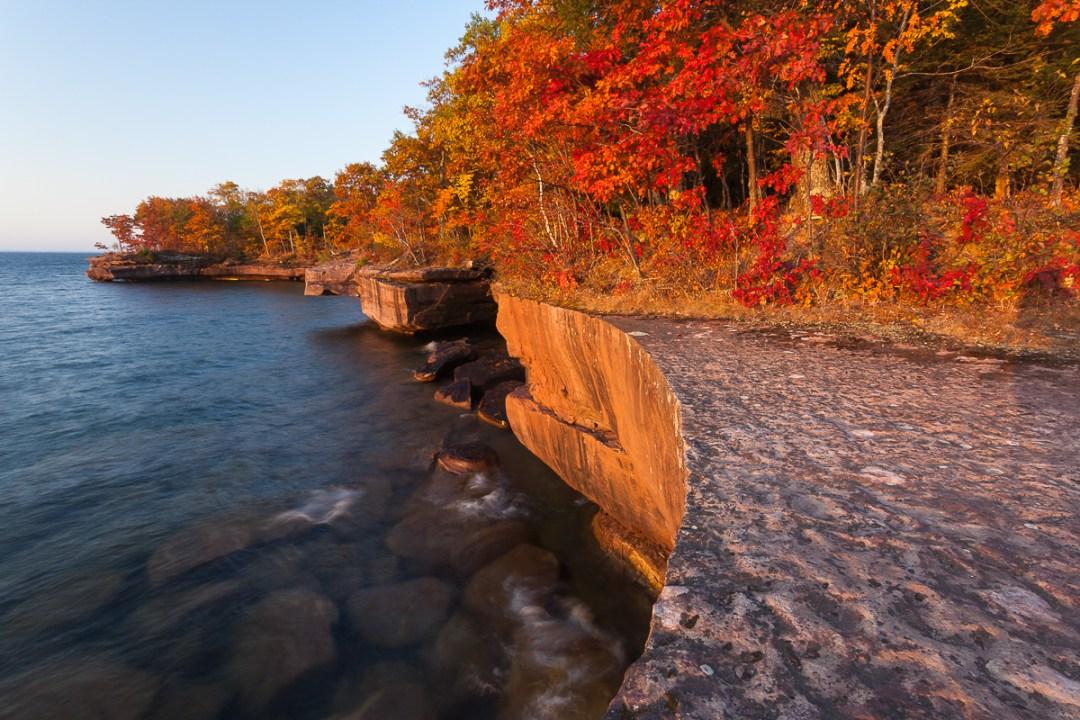 Sunrise on lakeshore cliffs in Autumn.