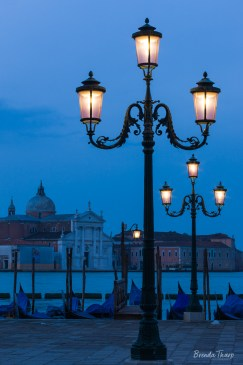 Traditional Lamps light up as dusk falls on St. Mark's Square in Venice, Italy.