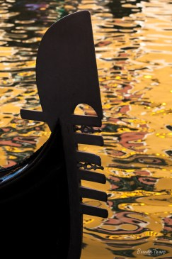 Silhouetted bow of a Gondola with colorful reflections on water in Venice.