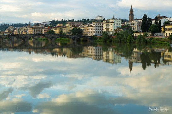 Tranquil reflection of Florence in river.