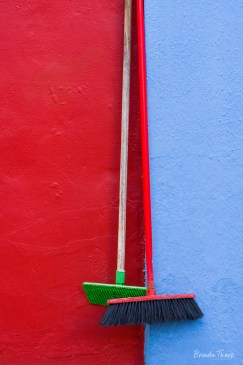 Cleaning brushes hang on colorful walls, Burano.