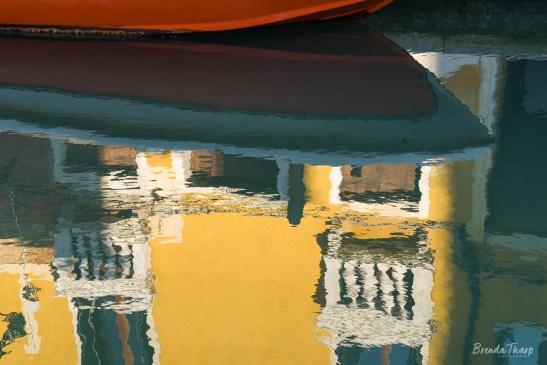 Red Boat and yellow walls reflected in canal, Venice.