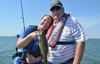 Becky Frazee Franklin was all smiles after landing a smallmouth bass on Coffey County Lake during a fishing trip with her dad (right) and guide Clyde Holscher.
