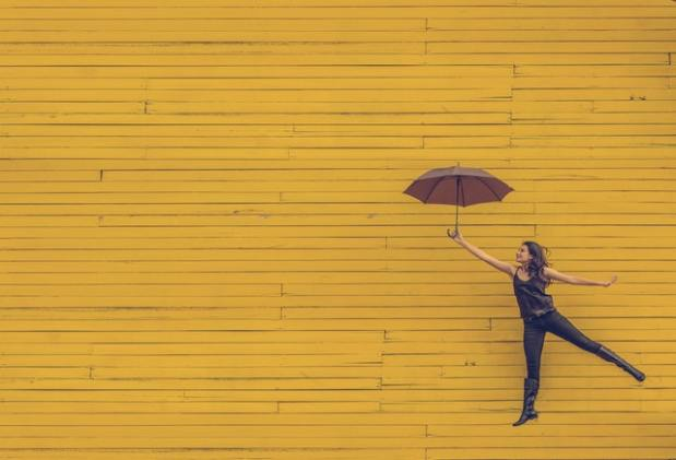 A young woman floating with an umbrella against a yellow wall