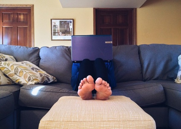 Man sitting on his couch with his laptop