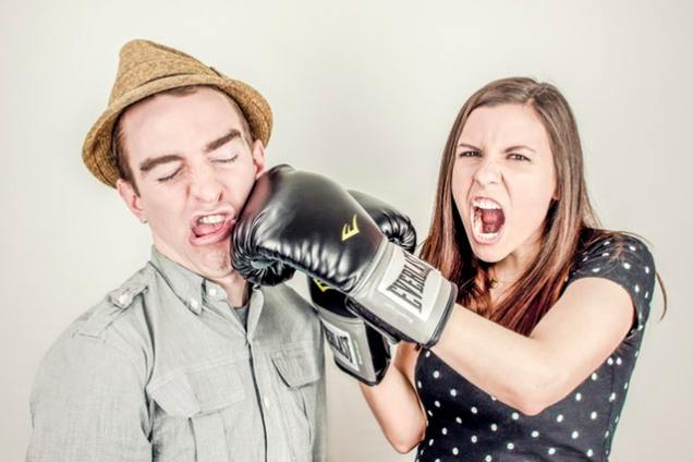 Woman playfully punching her husband with a boxing glove