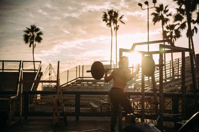 Man lifting weights at sunrise
