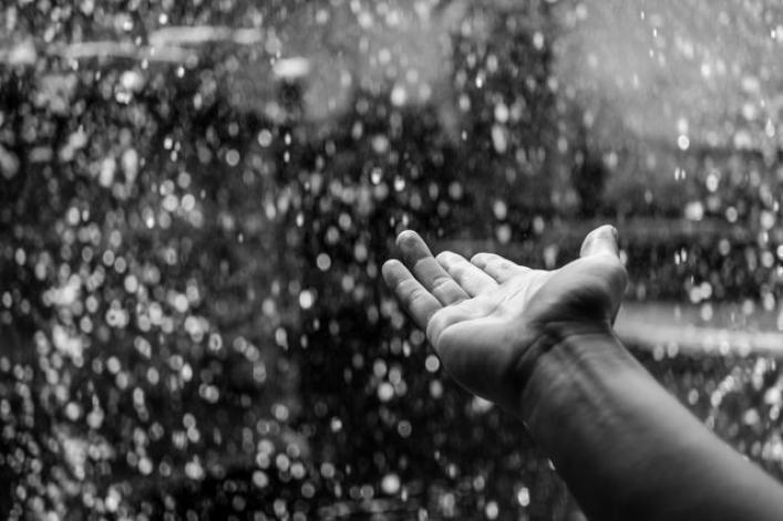 A hand extended into the falling rain