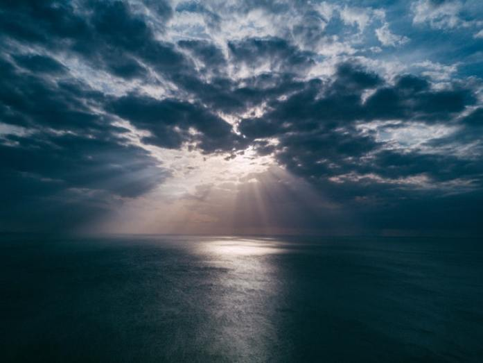 Sun rays breaking through dark clouds over the ocean