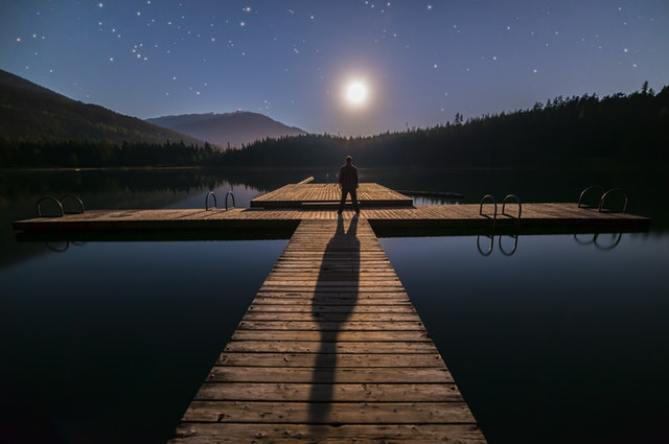 Man standing on a dock watching the sunrise