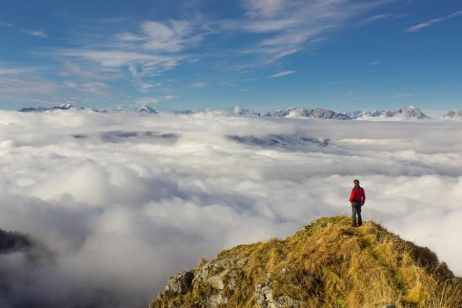 Man on a mountaintop looking out over the clouds