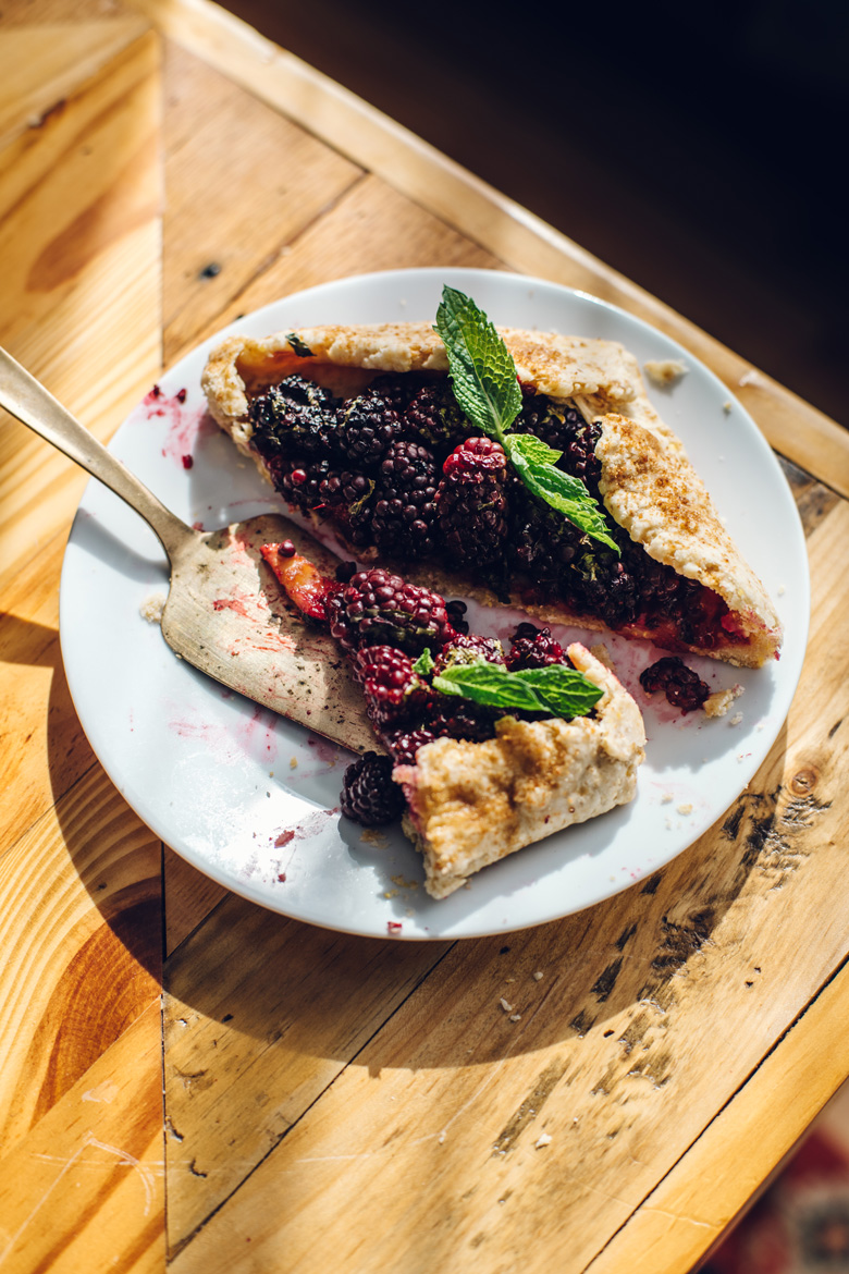 a half eaten blackberry galette on a plate in the sunshine