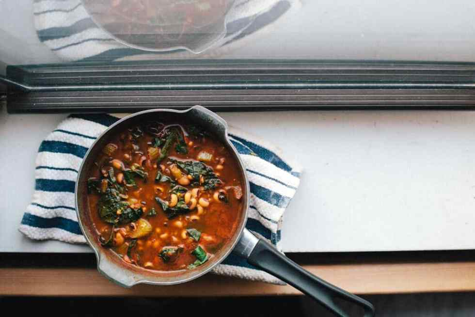 Overhead View of Meatless Black Eyed Pea Soup on a Windowsill. You Can See the Reflection of the Soup in the Window.