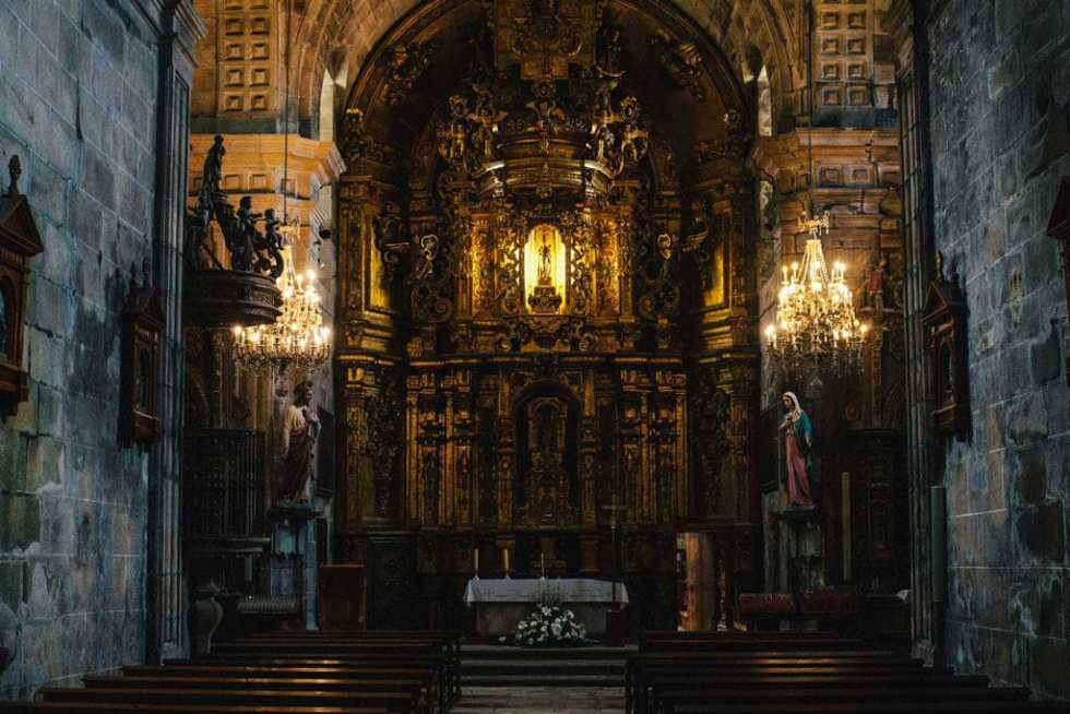 The inside of an old Spanish Catholic cathedral, lit by chandeliers.