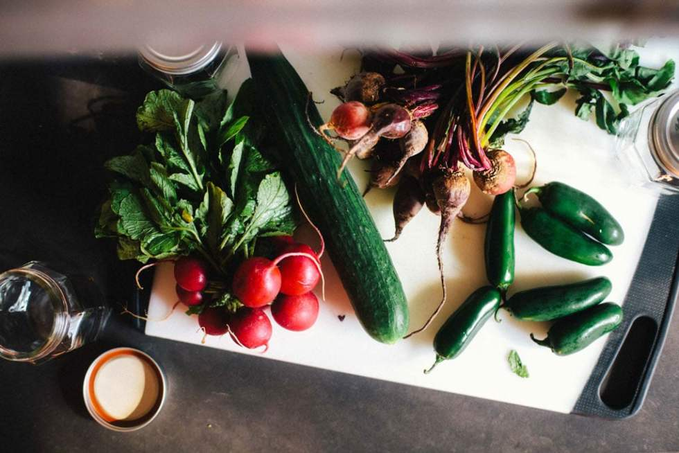 An overhead view of a cutting board with radishes, jalapenos, beets, and a cucumber.