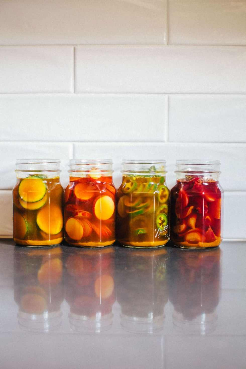 These sweet turmeric pickles are the BEST and most flavorful pickles you'll ever eat. There's no refined sugar, and the turmeric adds anti-inflamitory properties. All you have to do is decide what you want to pickle! (I suggest cucumbers, beets, radishes, and jalapenos!) #vegan #pickles #turmeric #healthy #recipe