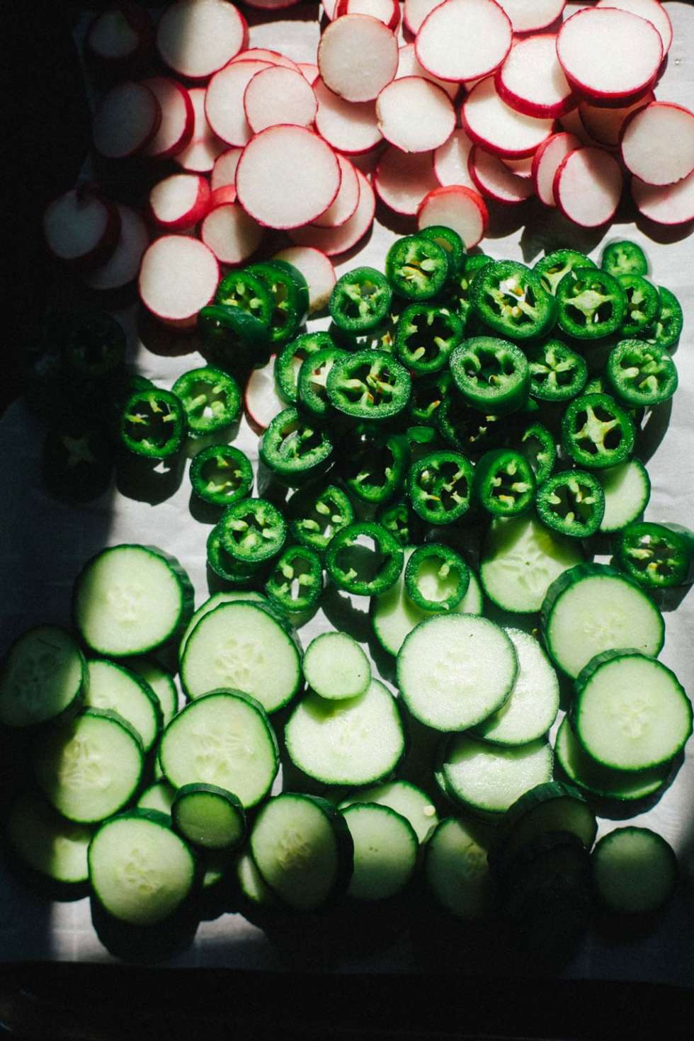 A cutting board with thinly sliced radishes, jalapenos and cucumbers.