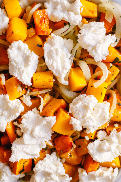 A close up of a casserole packed with squash, sweet potato, ricotta, and onions