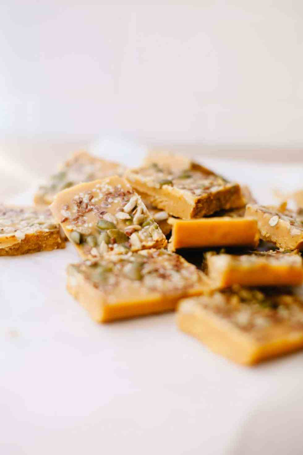 A stack of healthy pumpkin bark topped with hormone balancing seeds