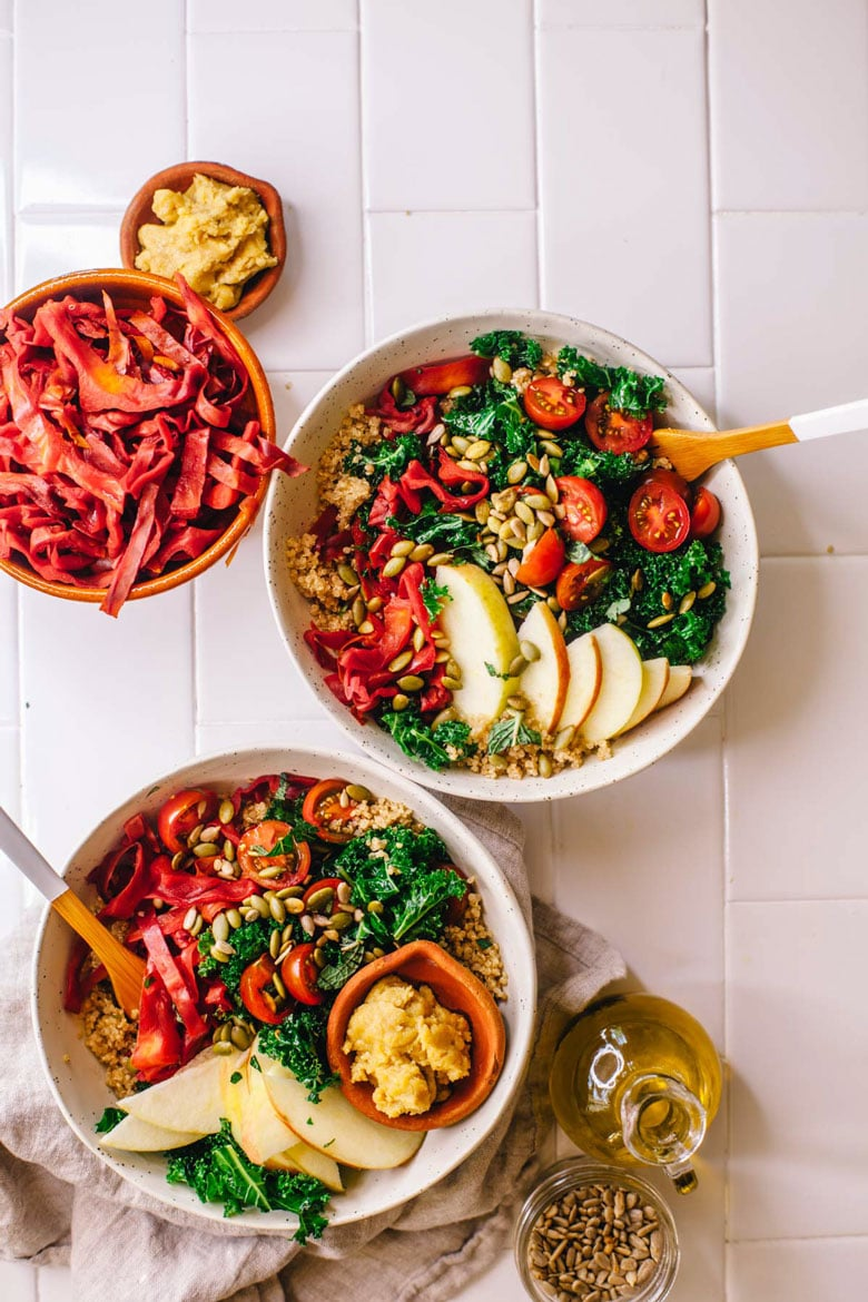"""Autumn Harvest Quinoa Bowl with kale, tomatoes, pickled cabbage, apples, pepitas, and an easy tahini-cashew """"cheese."""" #vegan #healthy #brewinghappiness"""