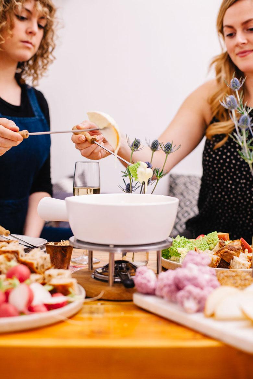 two girls sharing cheese fondue