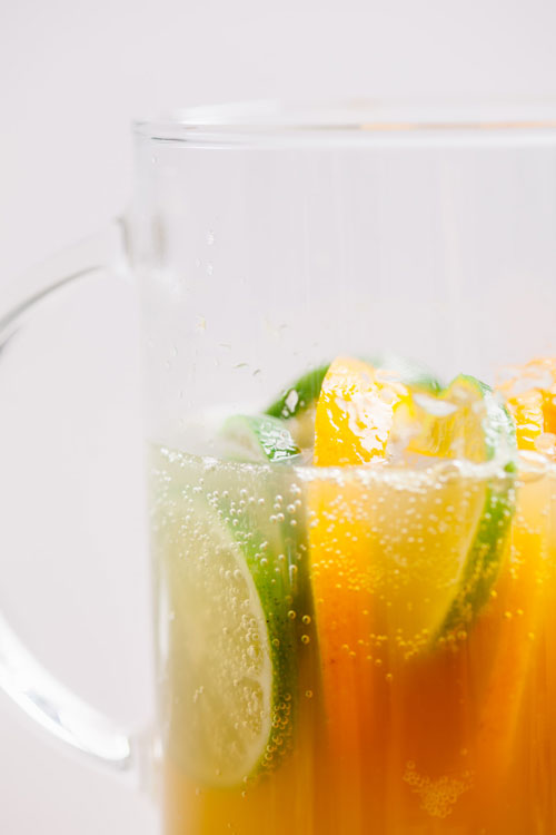 close up of orange and lime slices in a pitcher