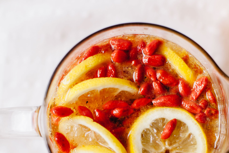 overhead view of lemons and goji berries in a pitcher