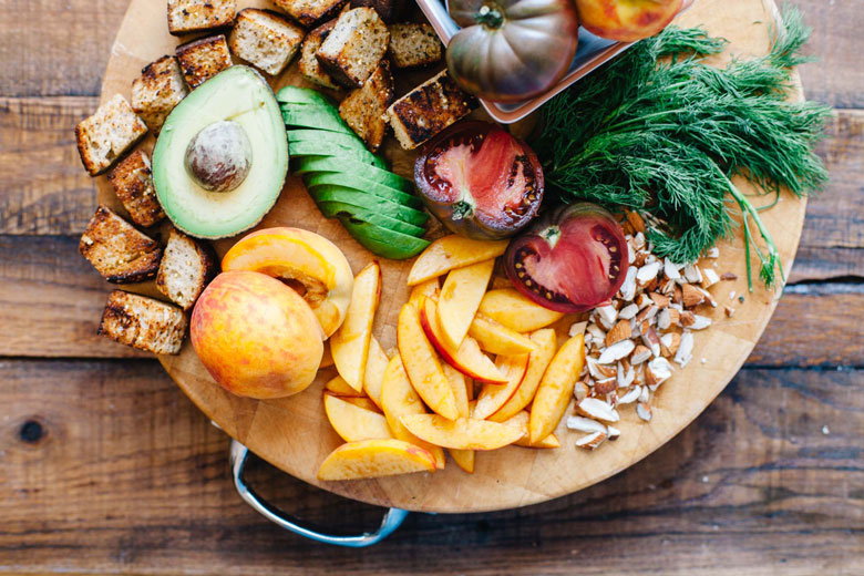 bread cubes, avocado, peaches, tomatoes, almonds, and fresh dill