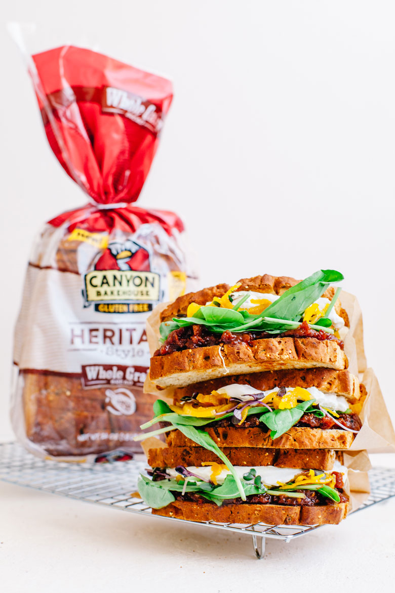 Three BLT sandwiches stacked with a Canyon Bakehouse loaf in the background