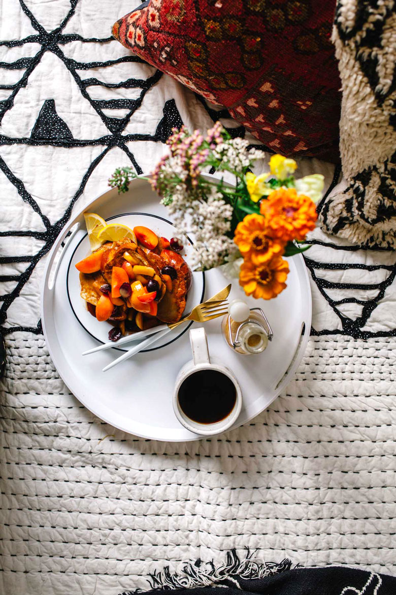 Tray with french toast, flowers, lemon tahini syrup, and coffee
