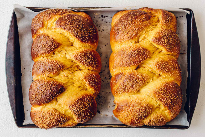 two loaves of maple pumpkin challah on a sheet pan