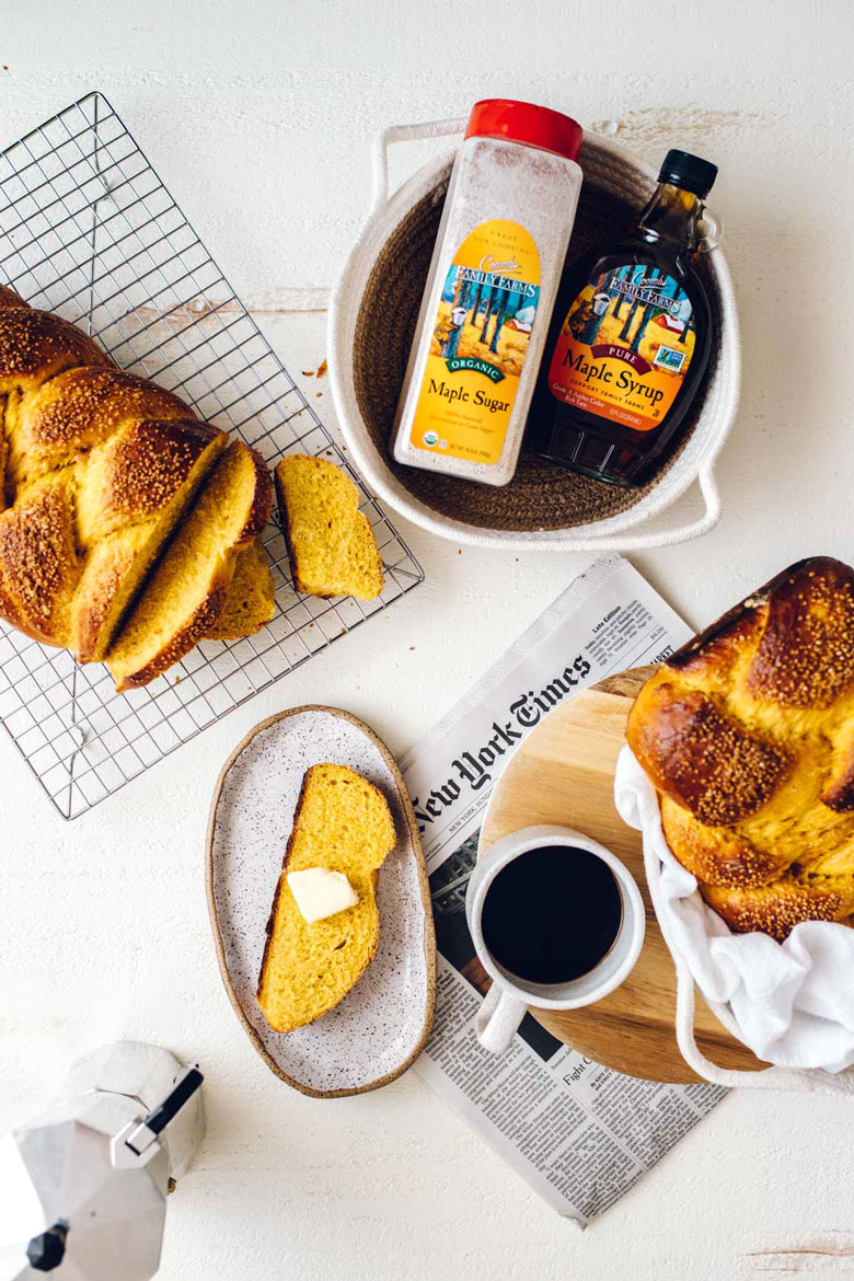 two loaves of maple challah, with Coombs Family Farms maple syrup in a basket, coffee, and a newspaper