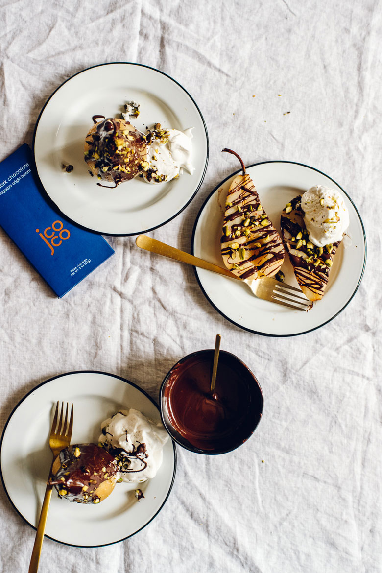 three rosé poached pears with jcoco dark chocolate drizzle, pistachios, and whipped cream