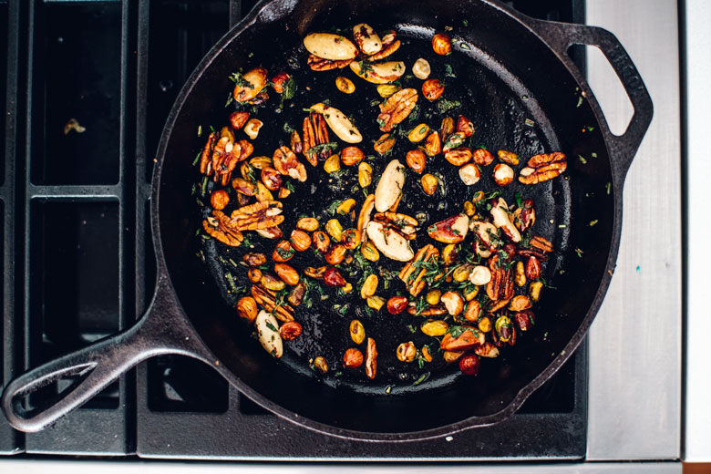 stovetop toasted nuts and herbs in a cast iron skillet