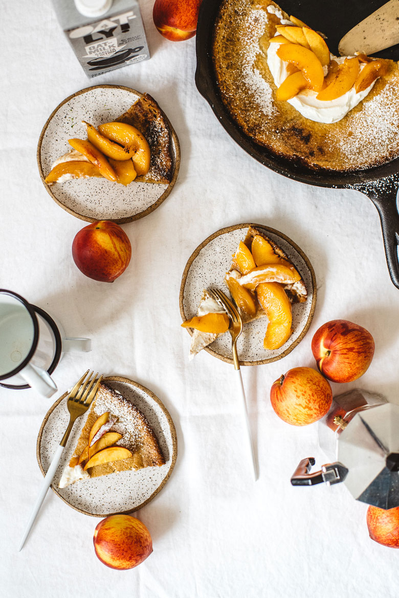 a peach oat dutch baby cut into three pieces on three small plates