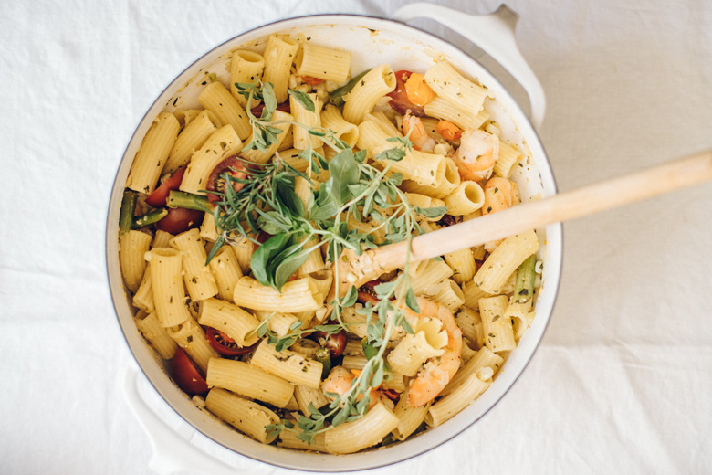 overhead shot of a large pot of pasta with fresh herbs on top