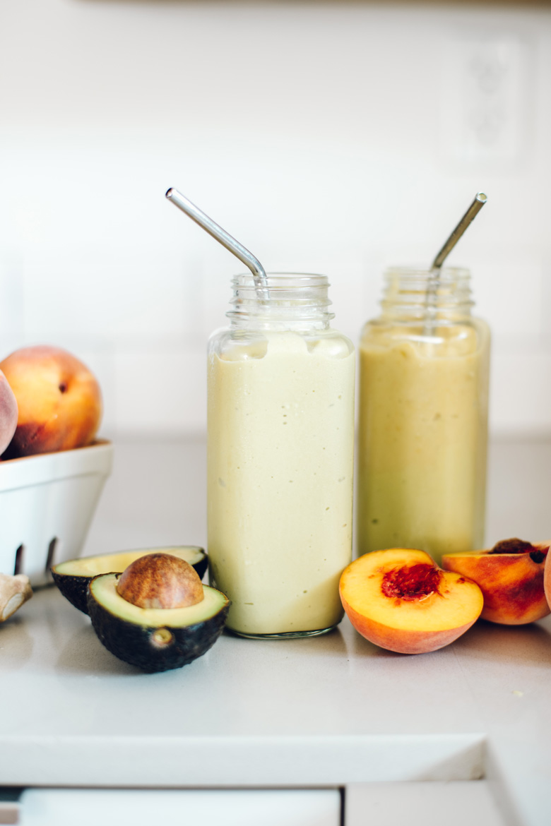 Two smoothies on a counter with straws, surrounded by fresh peaches and avocados