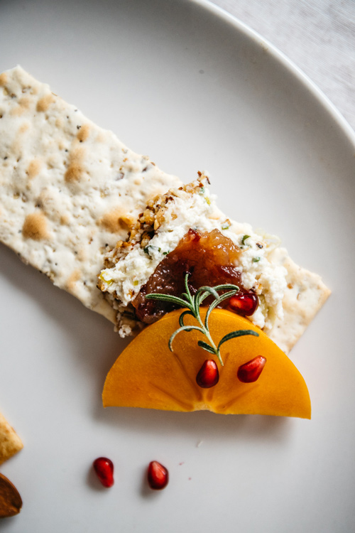 single cracker with nut cheese, cranberry fig jam, persimmon, rosemary and pomegranate