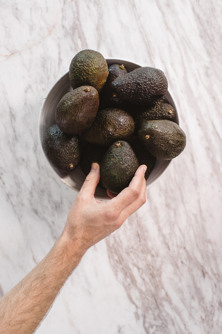 a hand reaching in to a bowl of avocados to judge their ripeness