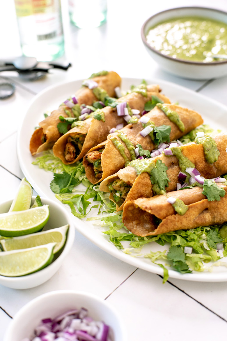 Side view of avocado chicken taquitos on a bed of lettuce and topped with avocado salsa verde