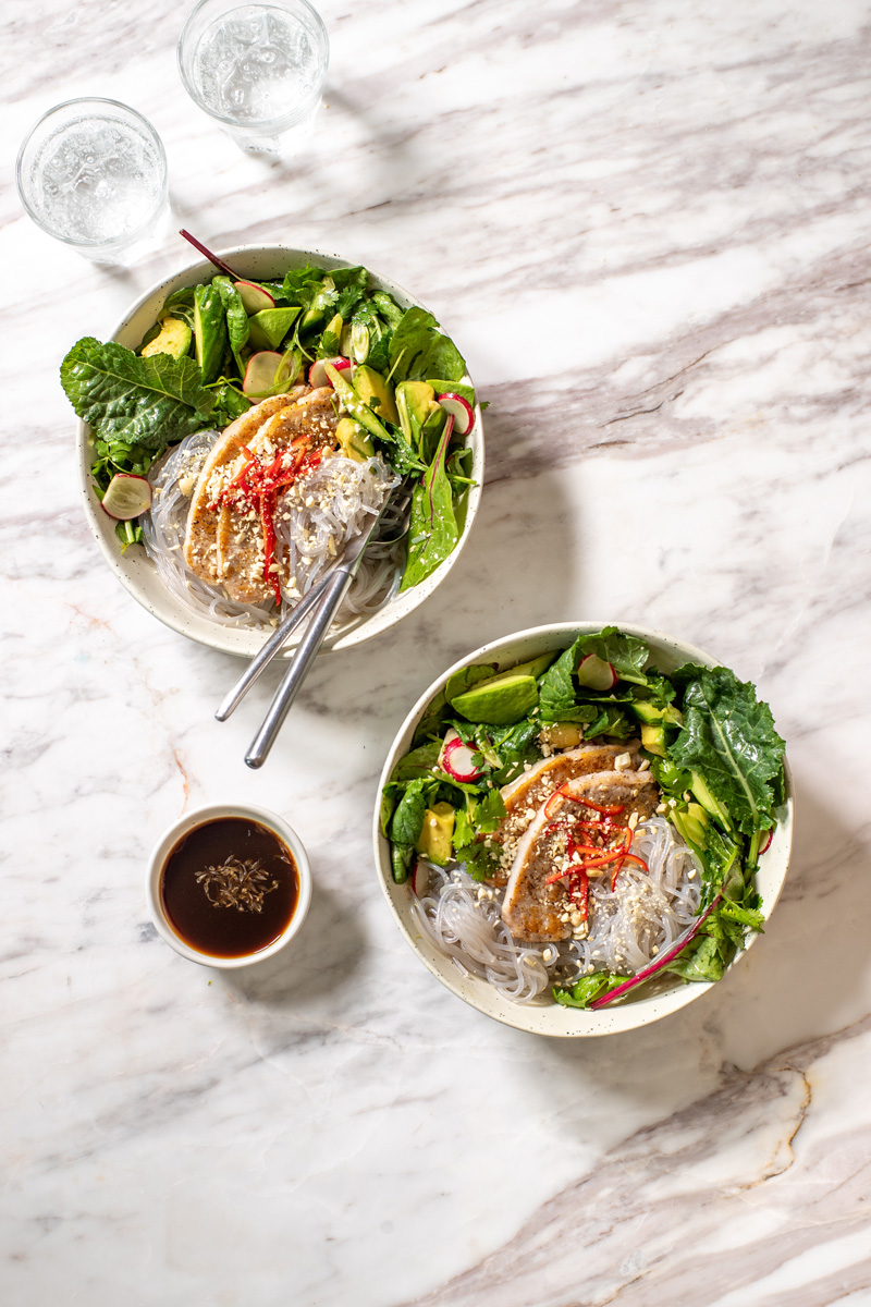 two bowls of glass noodle salad with pork chops on a marble counter with a small bowl of nuoc cham dressing on the side