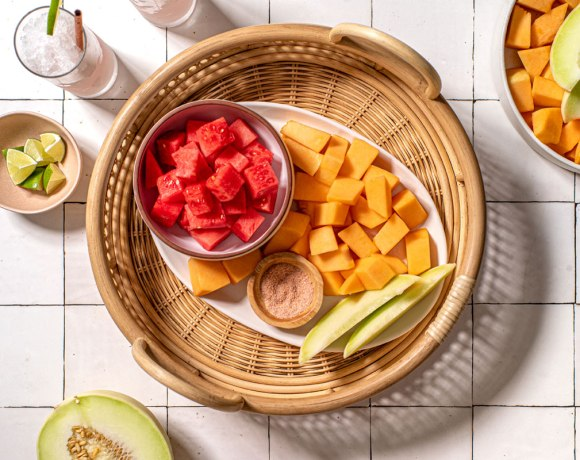 a wicker tray is in the center of the frame on a white tile surface. In the tray sits a bowl of cubed watermelon, cubed cantaloupe, and two slices of honeydew along with a small bowl of salt. Around the basket are frozen drinks, lime wedges, half of a honeydew, and a bowl of cubed cantaloupe.