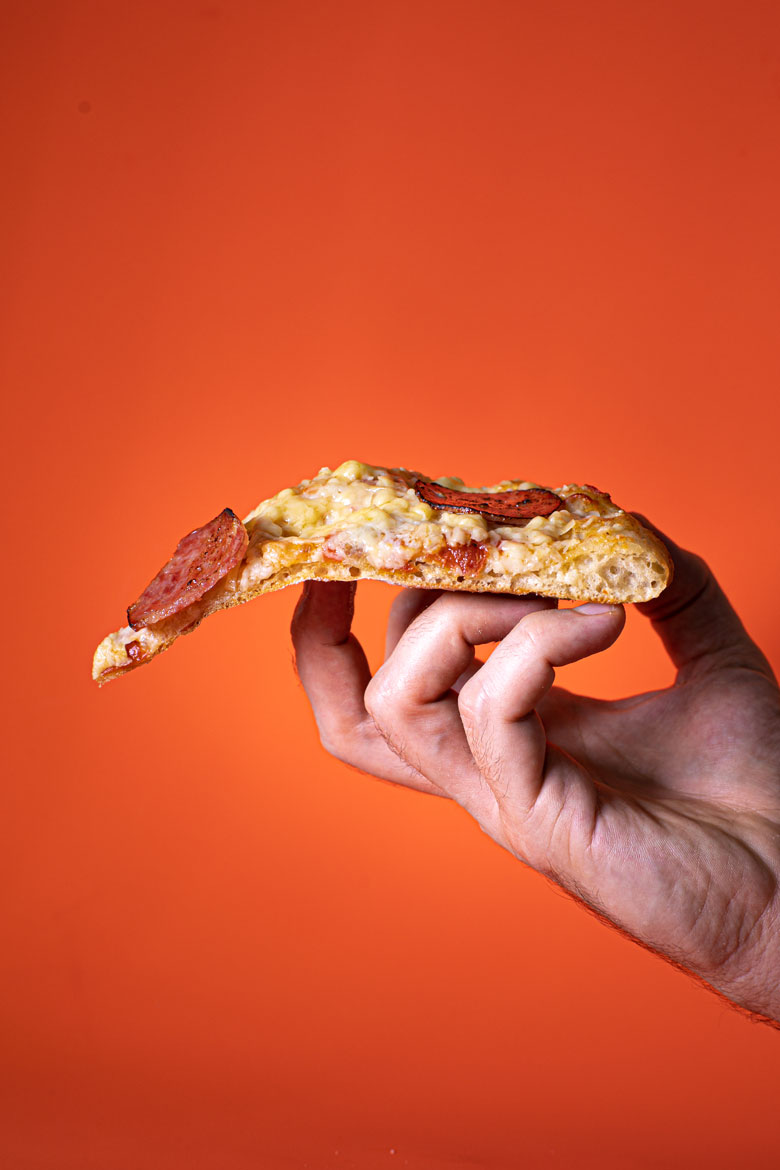 Male hand holding a single piece of pizza in his hand, against a red/orange background.