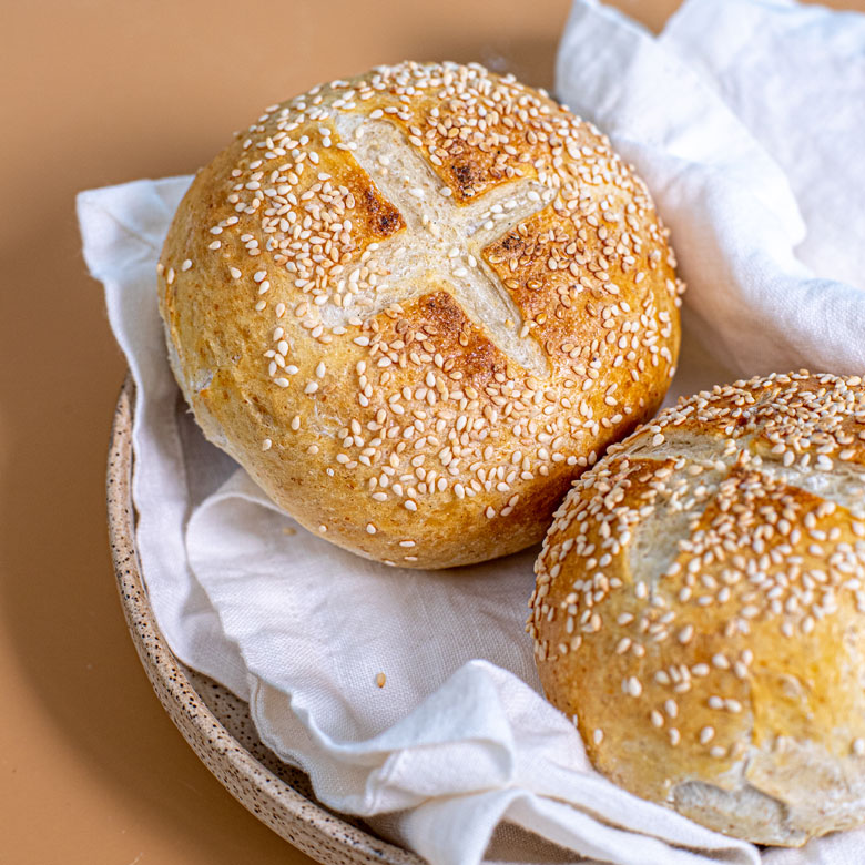 two rolls laying in a basket lined with a white towel. The rolls have an x-mark on top, and there are sesame seeds sprinkled on top.