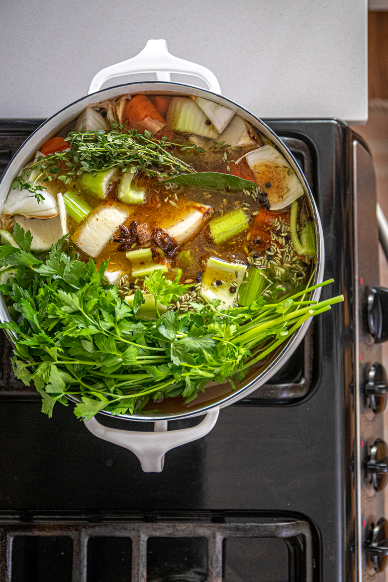 overhead view of a pot of chicken stock on the stove
