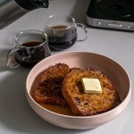 a pink plate with two pieces of espresso french toast sits on a grey countertop. On the french toast is a pat of butter and syrup. Behind the plate are two clear mugs filled with espresso