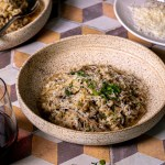 a bowl of creamy mushroom risotto sits on a colorfully tiled surface. In front of the bowl is a small bowl of chopped parsley, and behind the bowl to the right is a plate of parmesan cheese. Wine glasses with red wine are visible in the very back of the frame.