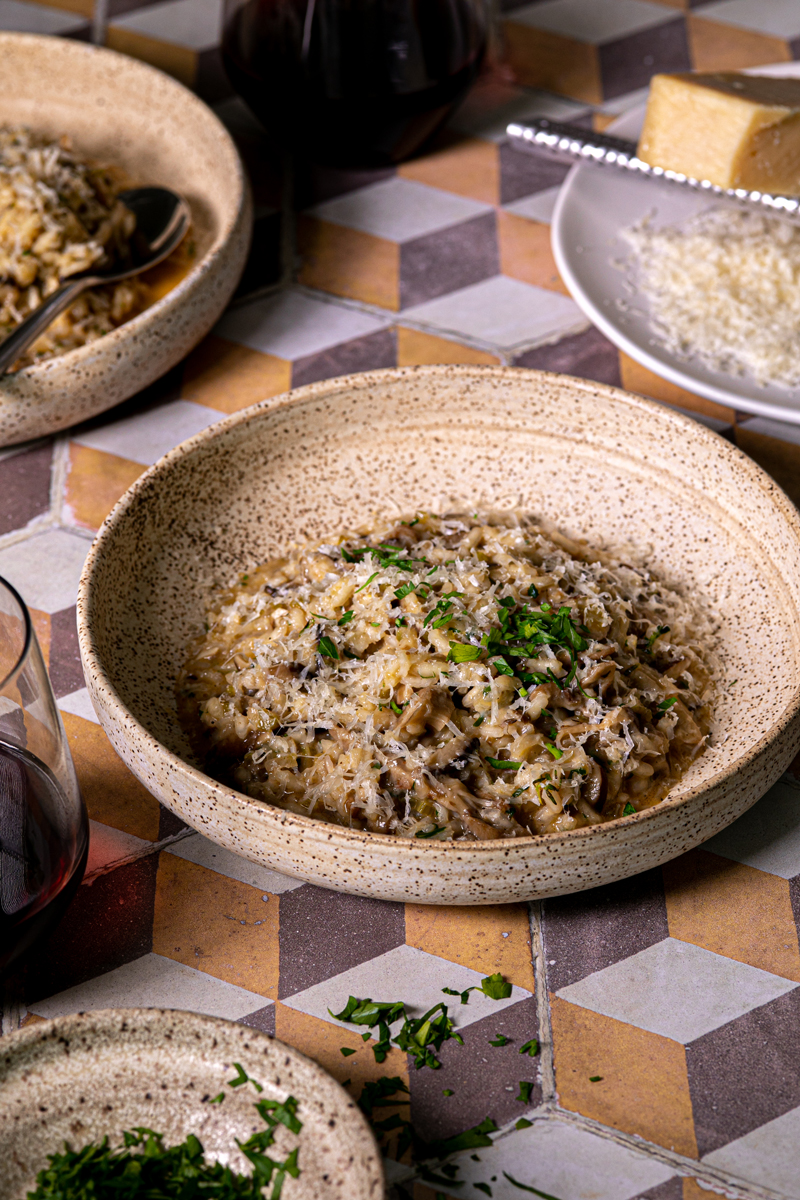 a bowl of creamy mushroom risotto sits on a colorful and geometric tiled surface. In front of the bowl is a small bowl of chopped parsley, and behind the bowl to the right is a plate of parmesan cheese. Wine glasses with red wine are visible in the very back of the frame.