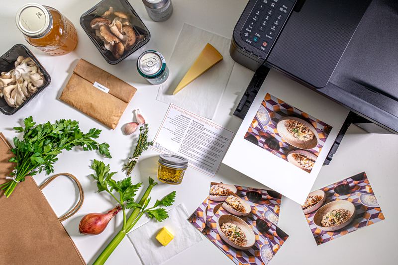 ingredients for creamy mushroom risotto are sitting in individual packages on a white surface along with the Canon PIXMA TR4520 printer, which has printed recipe cards for the meal kit