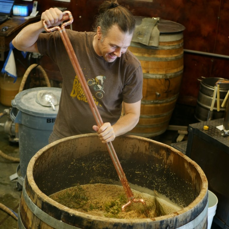 Adding fir branches to the mash at The Ale Apothecary